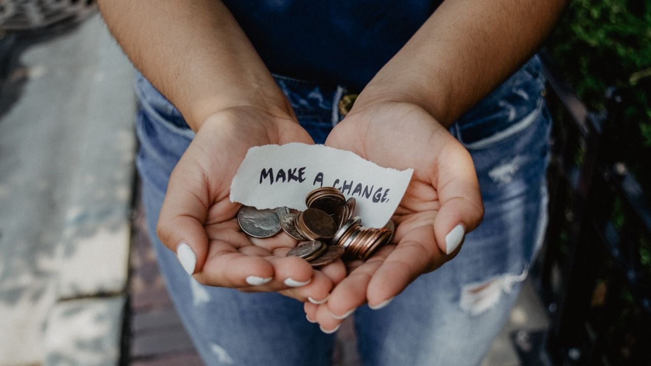 Hands holding money with Make a Change message
