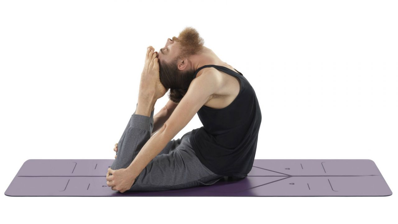 A man practising yoga on a purple Liforme mat