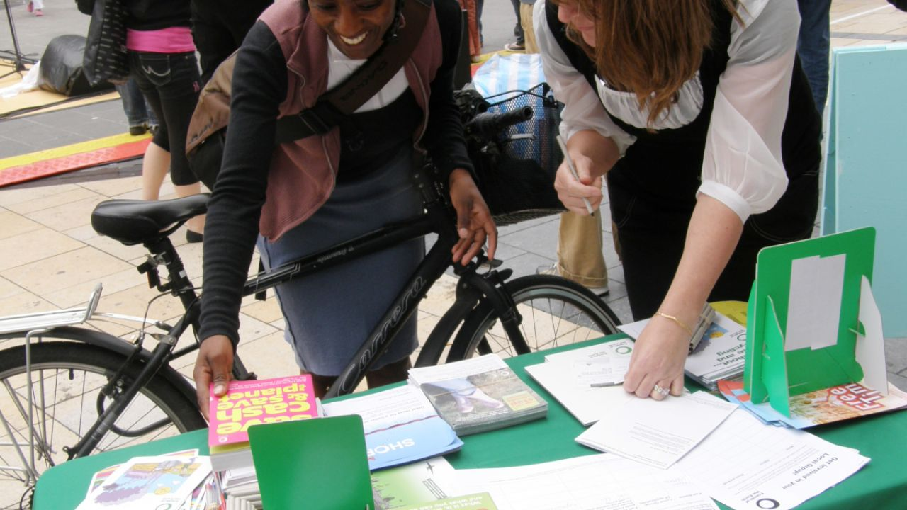 A cyclist looking at the materials on a Friends of the Earth local group stall