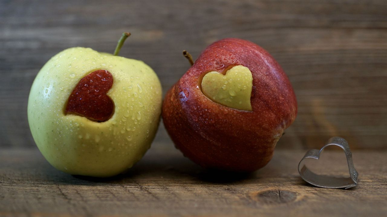 A red and a green apple with a heart shape carving