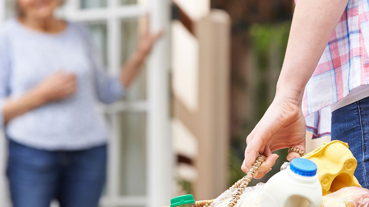 A woman gives a basket of surplus food to her neighbour