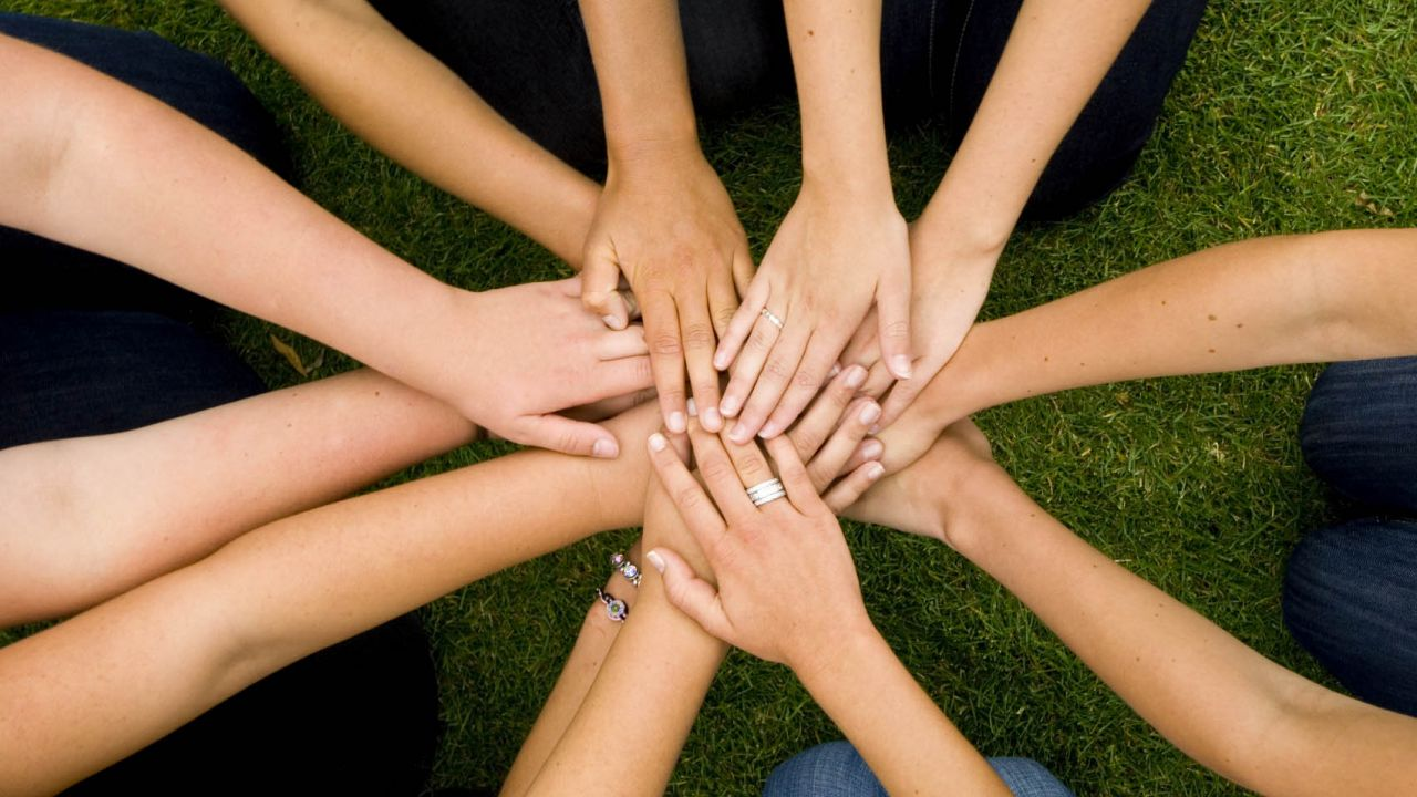 group of people joining hands