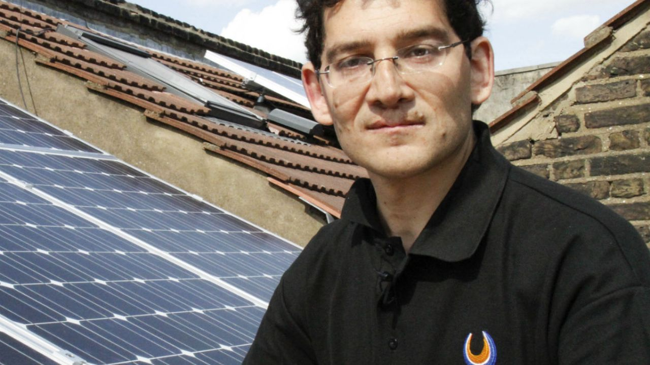 Phil Michaels next to solar panels on a terrace house roof