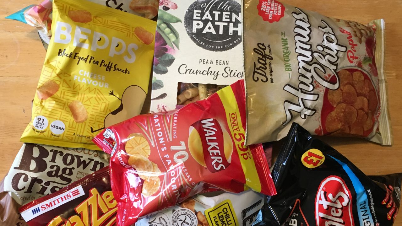 An assortment of plastic crisp packets and other snacks including Frazzles, Twiglets and Hummus Chips