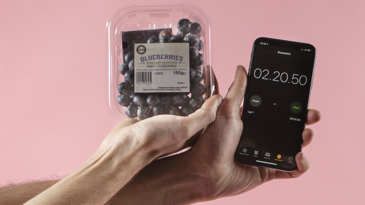 One hand holding a smartphone showing a timer screen and the other hand holding a plastic tub of blueberries
