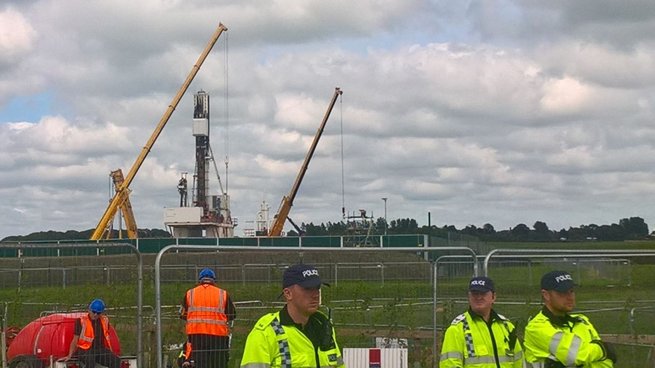 3 police guard the fracking site at Preston New Road, Preston, Lancashire. Site and 2 workmen in background.