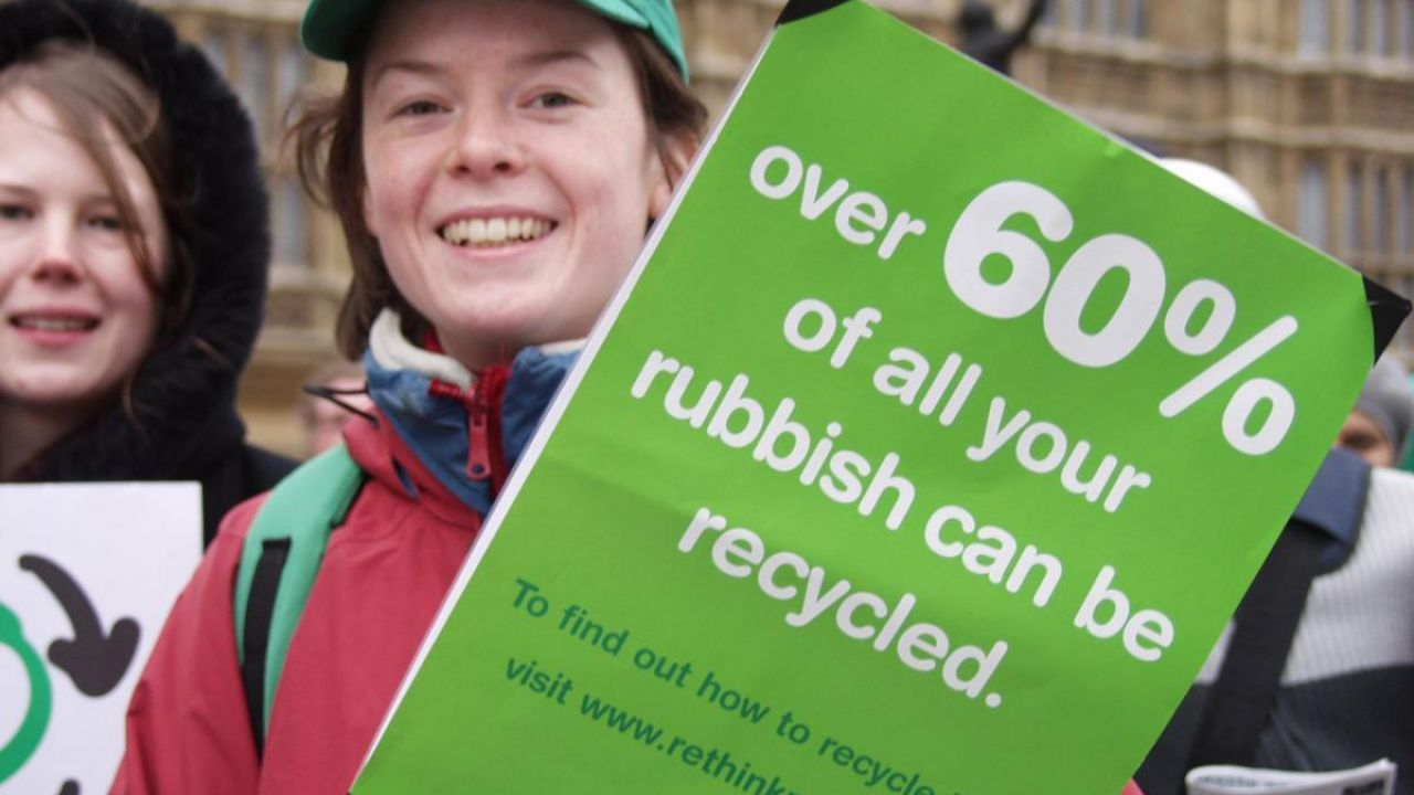 "Person holding a banner that reads ""Over 60% of your rubbish can be recycled"""