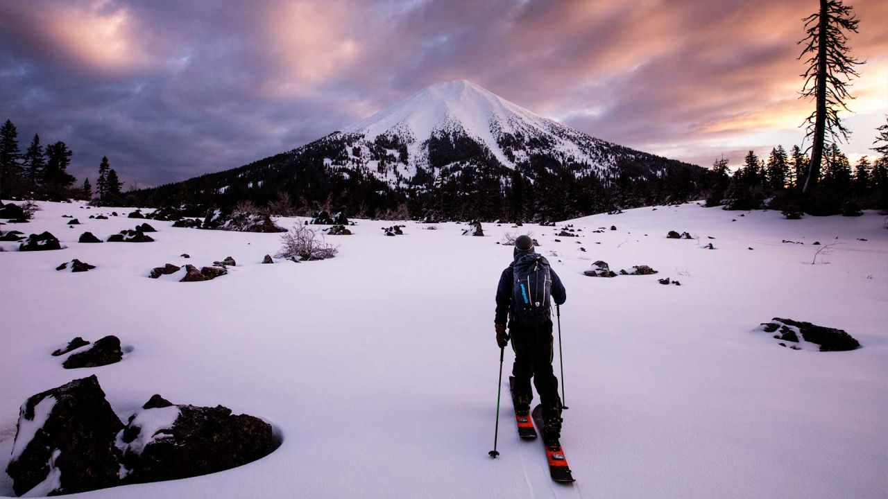 Cross-country skier in Patagonia clothes in front of mountain at sunset