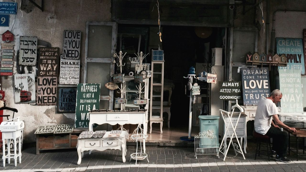 The shopfront of a secondhand store, selling old furniture and feel-good signs