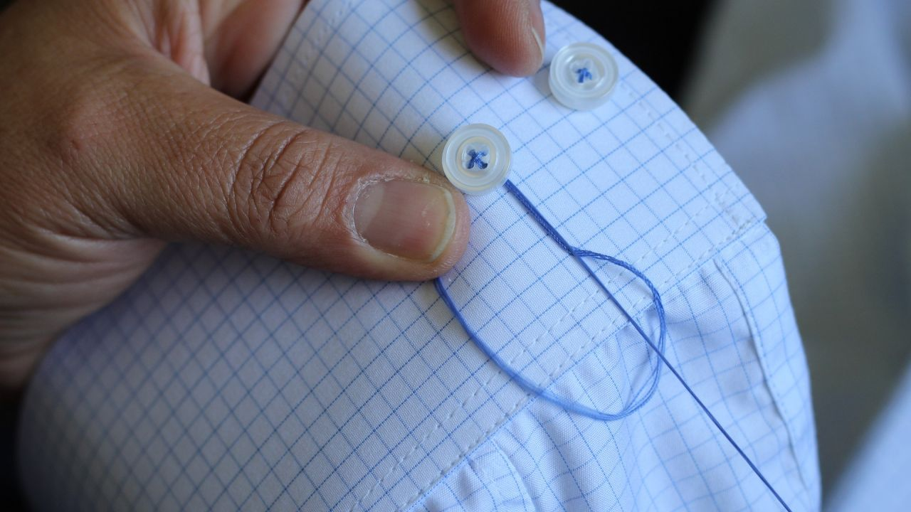 Sewing button back on to a shirt