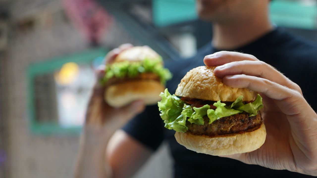 Person holding two vegan burgers