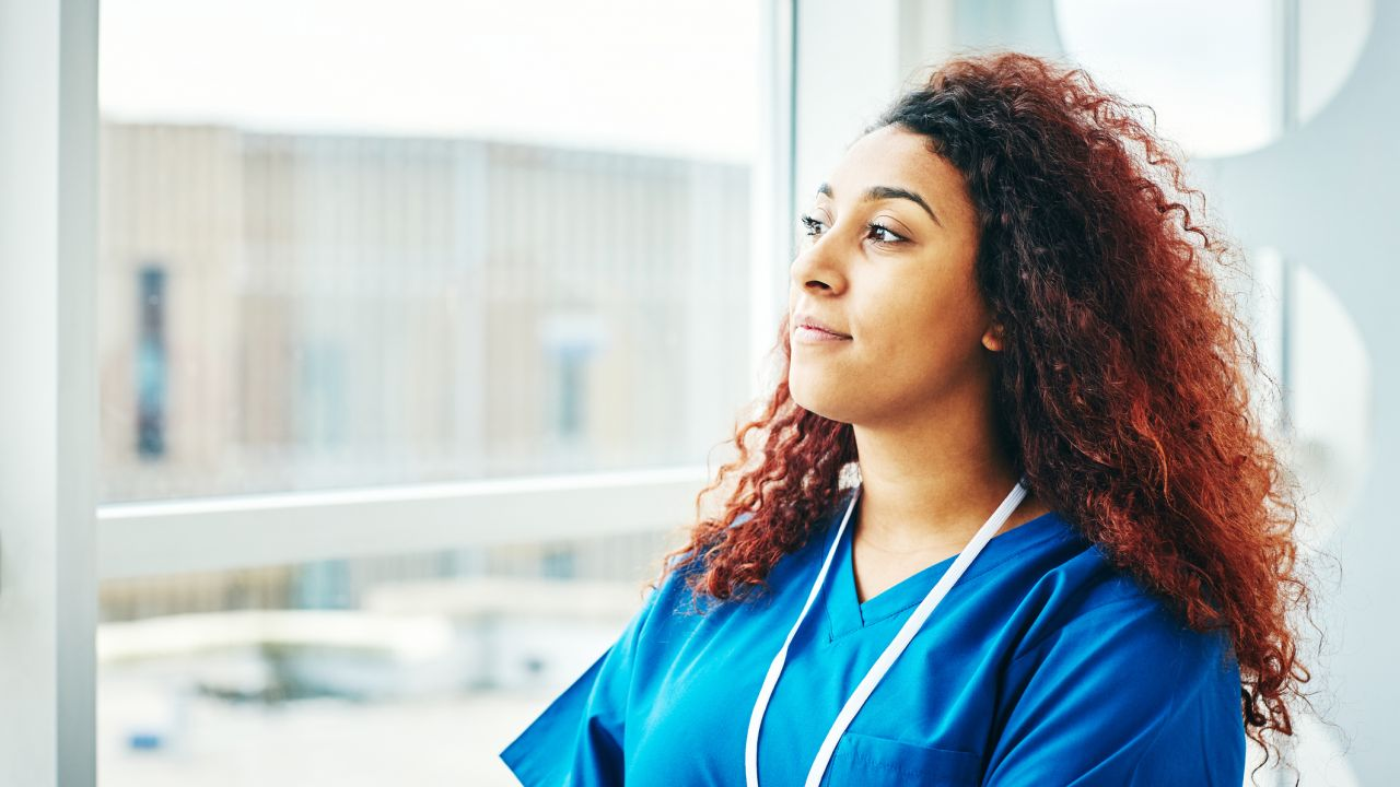 What can I do to stop climate change? A black female nurse looking out a window, deep in thought