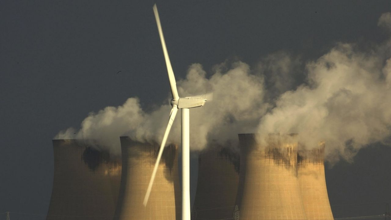 A wind turbine generates electricty in the shadow of Drax, Europe's biggest coal-fired power station