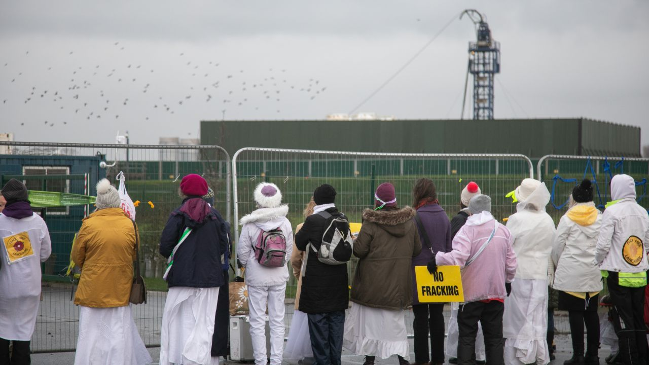Women in White stand in silence with their backs to the camera looking through the barrier at the Preston New Road fracking site