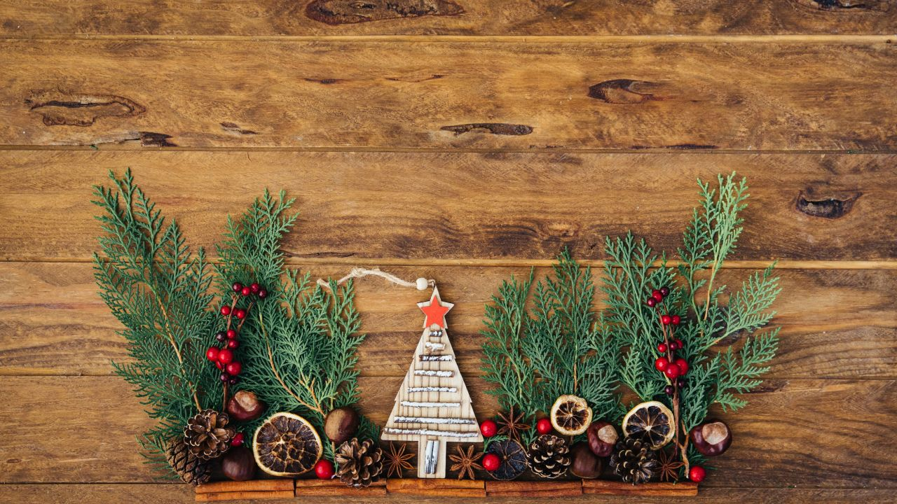 Christmas plastic free: decorations over a wooden background, including pine cones, pine leaves, dried orange and a miniature wooden Christmas tree