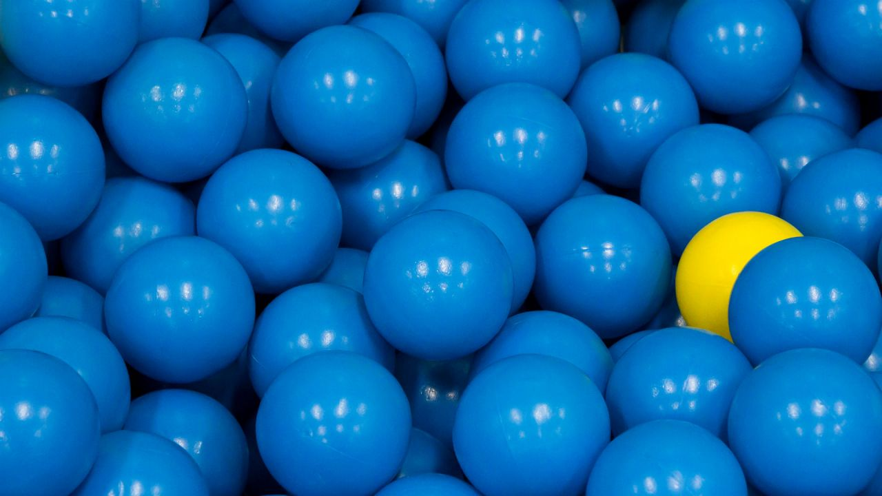 yellow plastic ball hiding among blue plastic ball