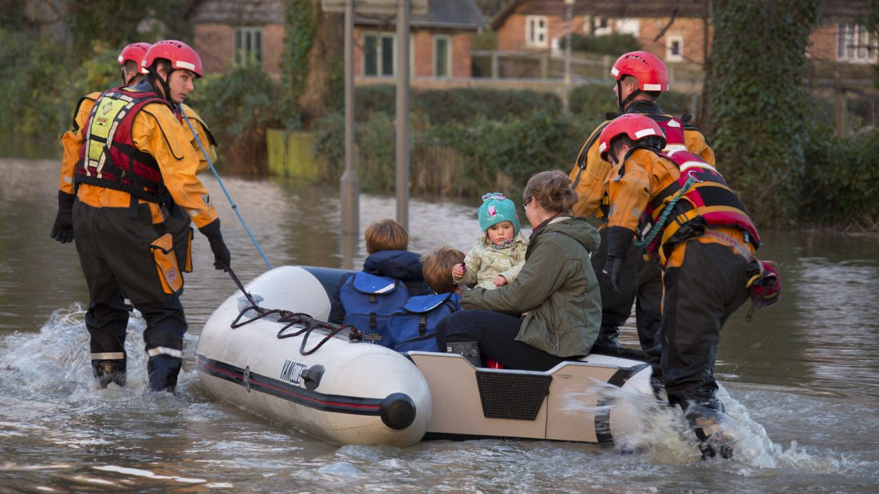 Young family being rescued in dinghy by the fire service after River Derwent burst its banks in the village of Old Malton in North Yorkshire.