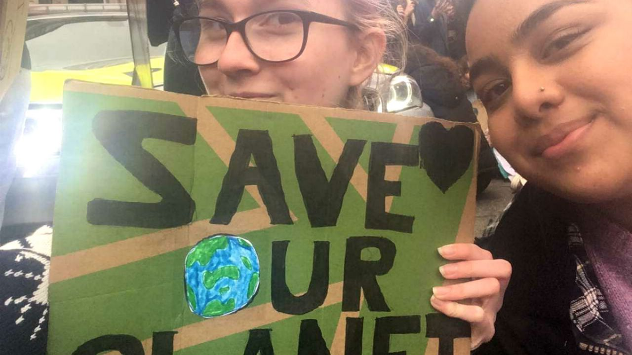 "Ummi with her friend holding up a banner that reads ""Save our planet"" at the Youth Climate Strike in London, March 2019."