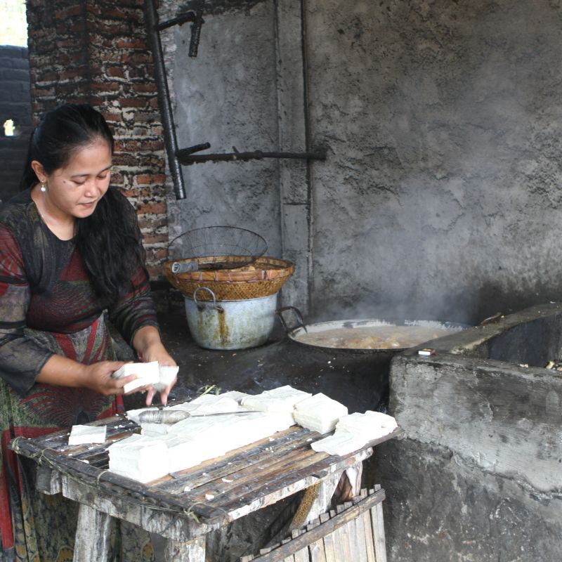 A woman fries tofu using plastic waste as a fuel