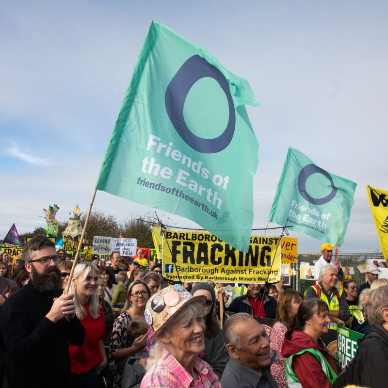A rally against fracking at Preston New Road, Lancashire. People can be seen holding anti-fracking and Friends of the Earth banners.