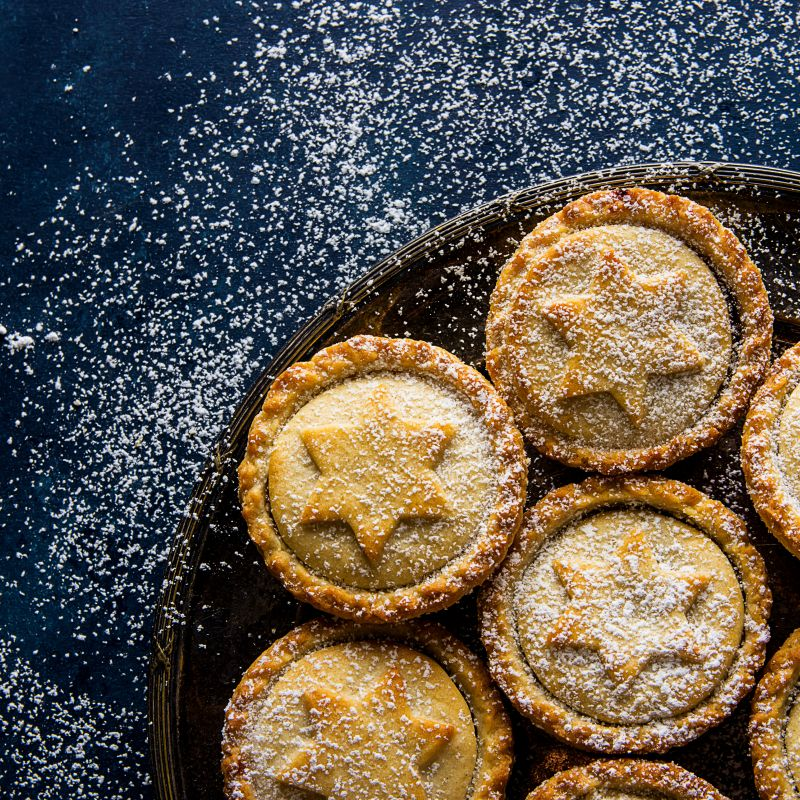 Enjoy Christmas plastic free: homemade mince pies with star-designed tops on a plate, dusted with icing sugar