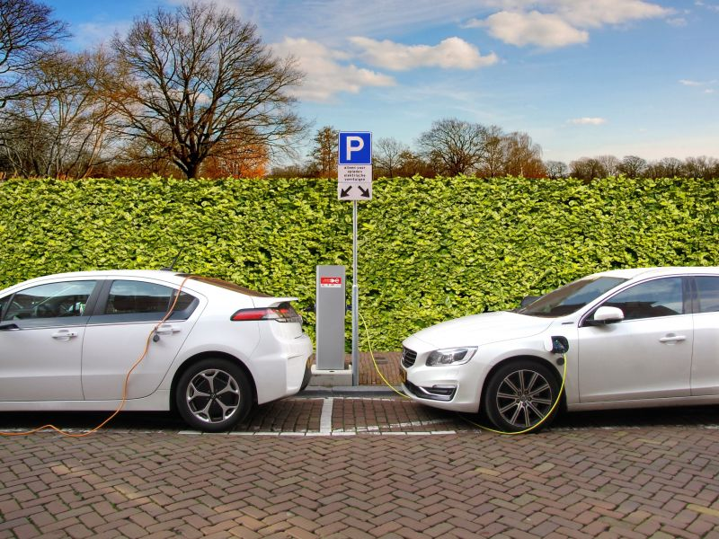 Two white electric cars charging while parked