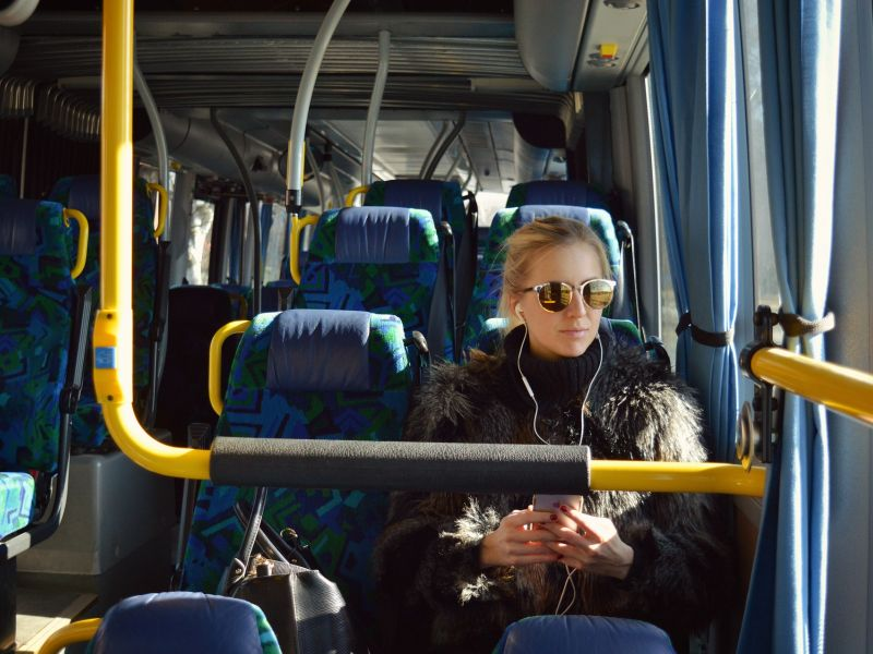 photo of passenger on a bus with earphones and sunglasses