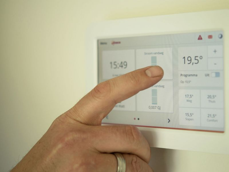A man's finger next to a smart energy meter display panel