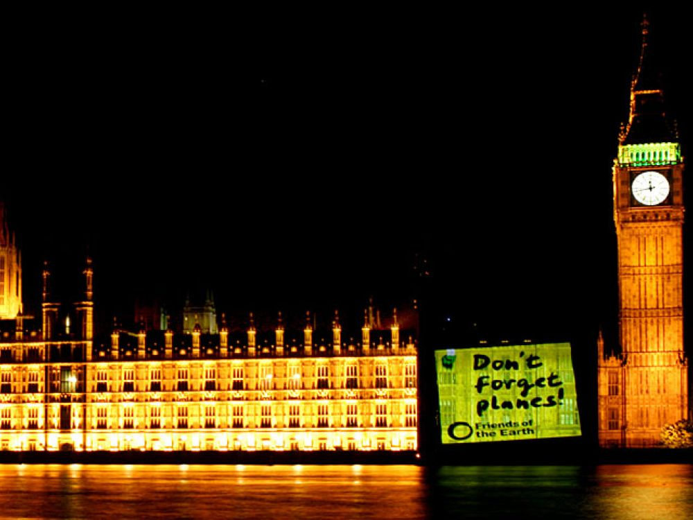 Post-it note projected onto the Houses of Parliament telling the government not to forget to include planes in the carbon targets