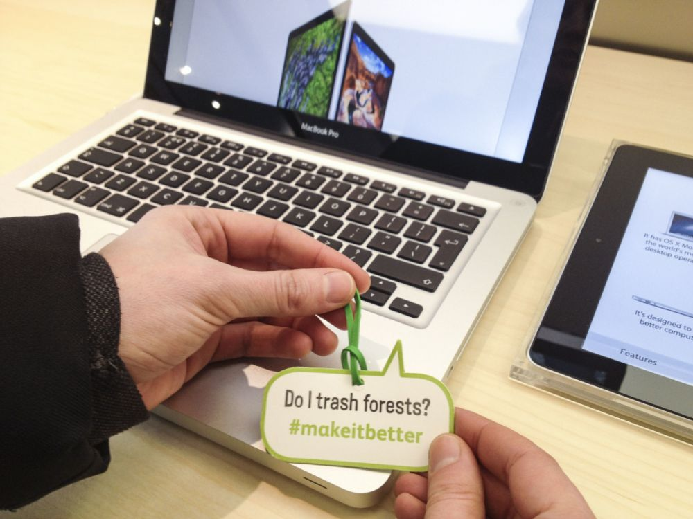 "Friends of the Earth attaches labels to Apple products at the opening of Apple's Leeds store, 21 March 2013. Part of the Make it Better campaign, the labels read: ""Do I trash forests?"" as a way of highlighting to comsumers the environmental impacts of Apple products."