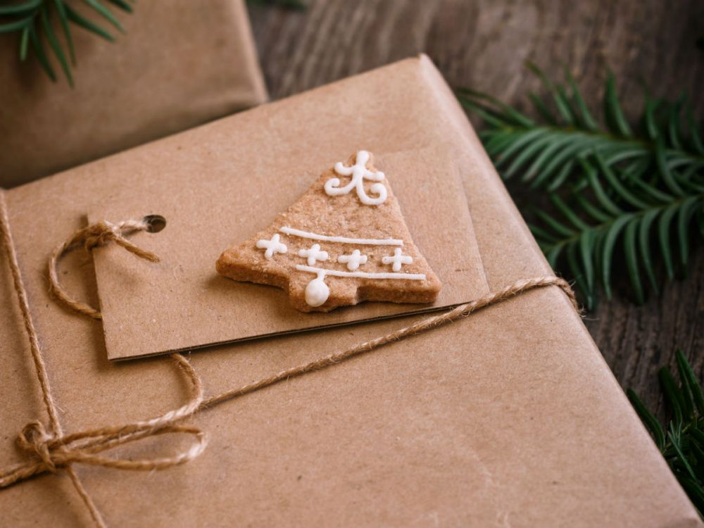 Christmas plastic free: a present wrapped in brown paper with a cardboard gift tag, decorated with a bell-shaped cookie.