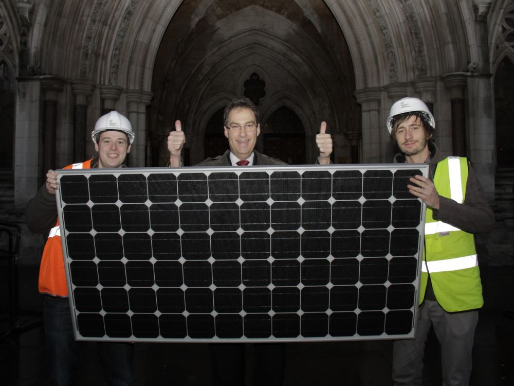 Friends of the Earth Director stands in front of High Court after judge rules in our favour over government plans to cut solar funding. Andy is standing behind a solar panel flanked by 2 campaigners pretending to be solar engineers