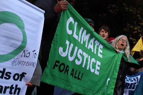 Friends of the Earth protesters holding a Climate Justice For All banner