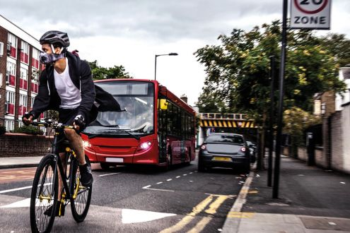 Cyclist wearing breathing mask, on road with bus and cars