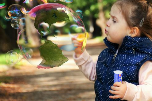 Infant girl blowing bubble with annotated globe inside it