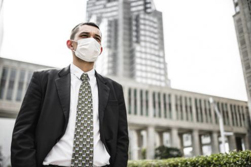 Man in suit and tie wearing face mask, standing outside large office blocks.