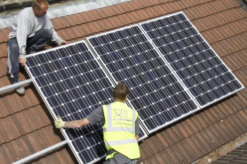 Two solar power engineers fitting solar electricity panels to a roof in North London, UK, 2011.