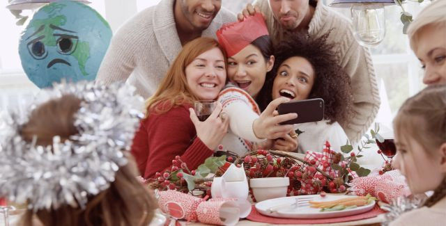Friends taking a Christmas selfie with the planet being left out