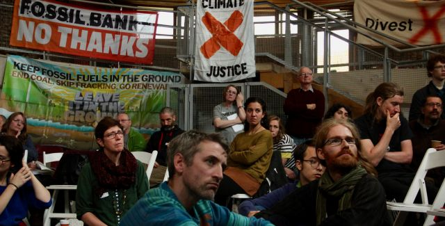A group of people listen at a talk on divestment in 2019