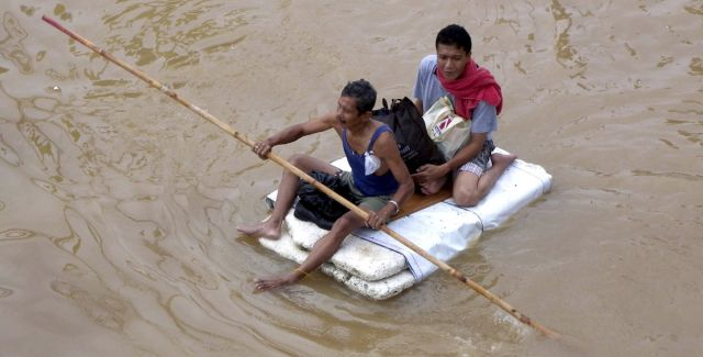 Two people on a make-shift raft during flood in Jakarta, Indonesia, 2014