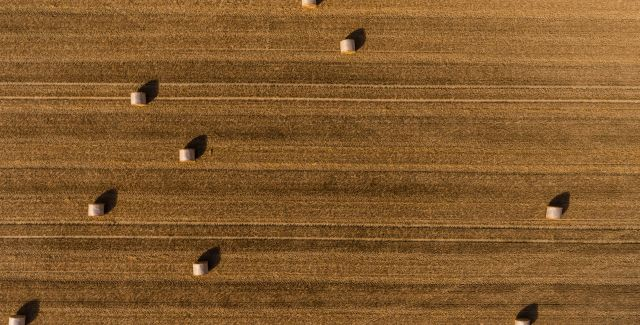 Very high birds eye view of hay bales on a field