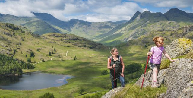 Woman and child hiking in stunning hilly landscape, Lake District National Park