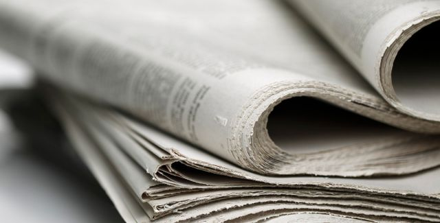 Shallow depth-of-field photo of a stack of newspapers