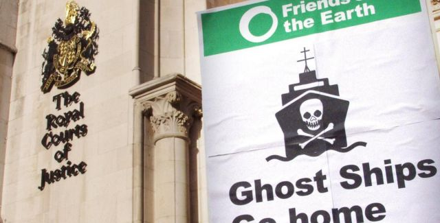 "A banner saying ""Ghost ships go home"" held in front of the High Court"